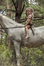 Garotinho sente-se no cavalo branco