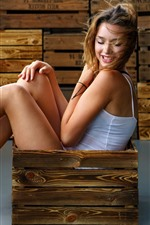 Smile girl sitting in wood box