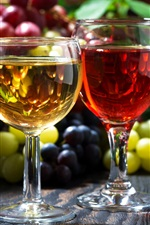 Two glass cups of wine, grapes