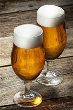 Two glass cups of beer, wood board