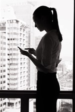Preview iPhone wallpaper Girl use phone, window, black and white picture