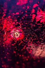 Glass surface, water droplets, backlight, light circles, red