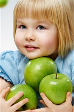 Blonde little girl and green apples