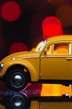 Yellow toy car, light circles, glare