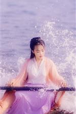 Chica de traje antiguo chino, juego guzheng en playa, olas del mar