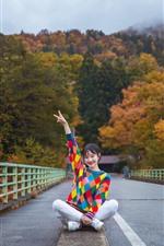Chica suéter colorido, pose, sentarse en el suelo, puente, árboles, otoño