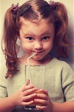 Cute little girl drinking orange juice