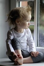 Little girl sit at windowsill, rain