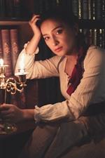 Chica de estilo retro, velas, llamas, libros