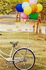 Bicicleta branca, balões coloridos, árvores