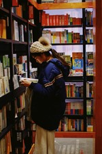 Preview iPhone wallpaper Girl reading book, book shop