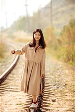 Preview iPhone wallpaper Smile Asian girl walking on the railroad