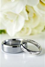 Wedding rings, flowers background