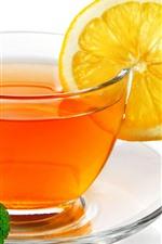 One glass cup of tea, lemon slice, green mint