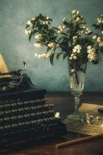 Typewriter, music score, flowers, vase