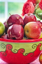 One bowl of red and green apples, red flowers