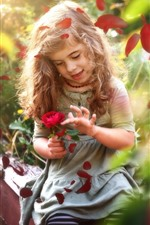 Cute little girl and red rose, petals, hazy