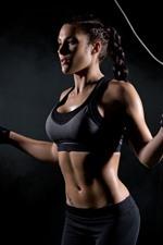 Fitness girl, black background, rope skipping
