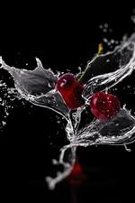 Duas cerejas, respingos de água, fundo preto