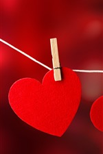 Two red love hearts, clothespins, rope
