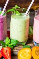 Three cups of smoothies, cocktail, strawberries, apricots