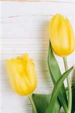 Preview iPhone wallpaper Three yellow tulips, green leaves, wood background