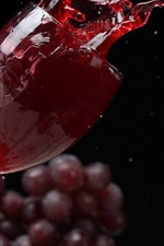 Red wine splash, glass cup, grapes, black background