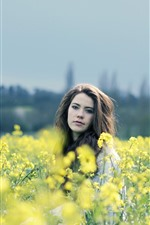 Girl in rapeseed flowers field