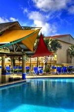 Pool, resort, buildings, palm trees, blue sky