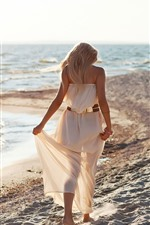 Blonde girl, back view, walk on beach, sea