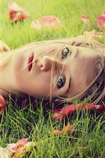 Blonde girl, lying on grass, look