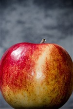 One red apple, gray background