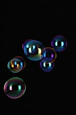 Preview iPhone wallpaper Some soap bubble flying, black background