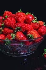 One bowl of fresh strawberries, black background