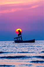 Um barco, mar, pôr do sol