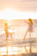 Счастливая девушка и мальчик играют воду, море, пляж, водный всплеск, лето