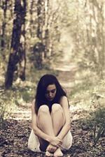 Menina solitária, sente-se no chão, árvores, grama, raios de sol