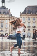 Menina de cabelo castanho jogar água, respingo, cidade