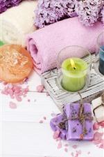 Velas coloridas, toalha, sabão, flores lilás, spa