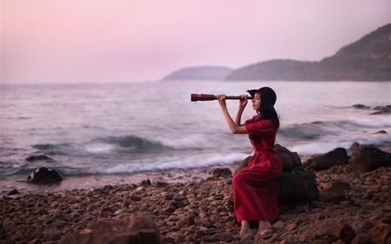 Обои Девушка из красного платья использует бинокль, море, камни