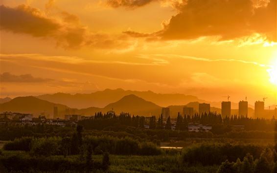 Fondos de pantalla Puesta de sol, cielo anaranjado, nubes, rascacielos, montañas, árboles