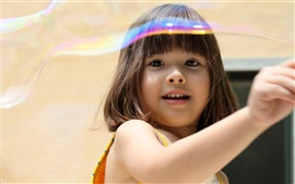 Cute girl play with soap bubbles