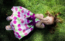 Preview wallpaper Lying on the grass of the cute little girl