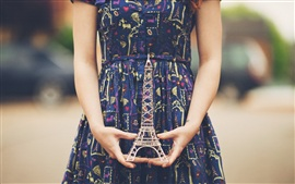 The girl hands Eiffel Tower model