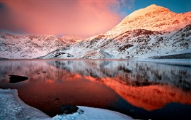 Winter lake, snow-capped mountains, the red glow beauty