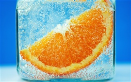 Close-up of orange slices in water, blue background, glassware, bubble
