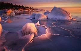 Las orillas de formación de hielo de invierno, el hielo de agua caliente, puesta del sol
