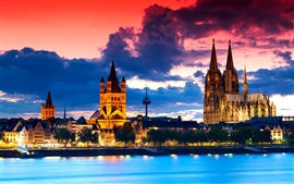 Gothic cathedral in Cologne, Germany, city night, river, clouds