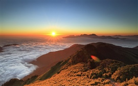 High-altitude mountain sunrise, floating clouds, sun