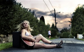 Music-loving girl, sitting on the side of the road, play the guitar